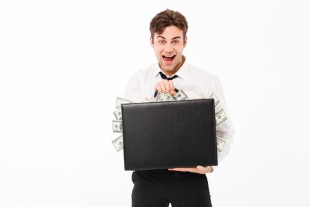 Ritratto di un uomo d'affari allegro felice che mostra la valigetta piena di banconote denaro isolato su sfondo bianco