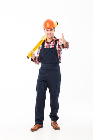 Full length portrait of a smiling young male builder holding spirit level tool while standing and giving thumbs up isolated over white background Reklamní fotografie