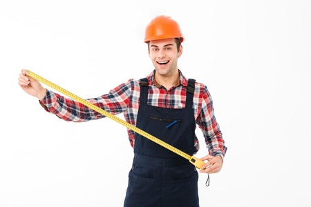 Portrait of a happy young male builder showing yellow measuring tape while standing and looking at camera isolated over white background Stock Photo