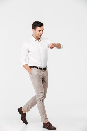 Full length portrait of a happy young man dressed in shirt looking at his wristwatch while walking isolated over white background