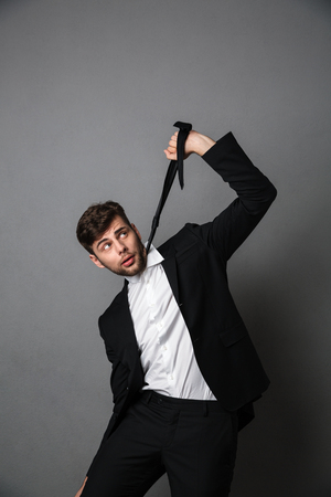 Desperate businessman strangling himself with a tie, isolated over gray background 写真素材