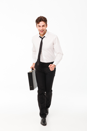 Full length portrait of a happy handsome businessman carrying briefcase while walking and looking at camera isolated over white background
