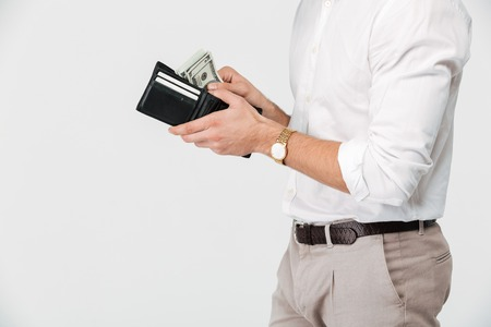 Close up of a man holding wallet full of money isolated over white background