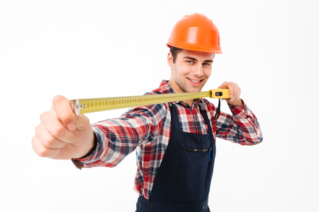 Portrait of a smiling young male builder showing yellow measuring tape while standing and looking at camera isolated over white background