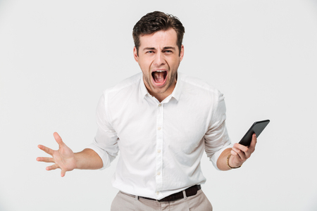 Portrait of a crazy angry man holding mobile phone and shouting isolated over white background