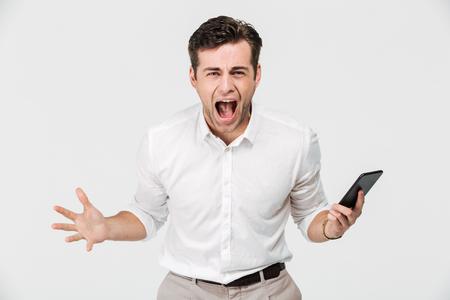 Retrato de un hombre enojado loco sosteniendo teléfono móvil y gritando aislado sobre fondo blanco Foto de archivo