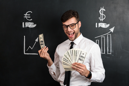 Happy young bearded man in glasses holding bunch of money, looking at camera, isolated over chalkboard with financial statistics