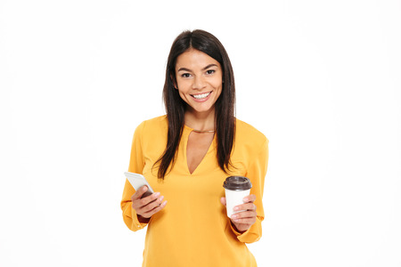 Close-up portrait of happy young brunete woman in yellow shirt holding cup of coffee and mobile phone, looking at camera, isolated over white background