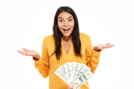 Portret van een tevreden gelukkige vrouw die bos van geldbankbiljetten ontvangen en camera bekijken die over witte achtergrond wordt geïsoleerd