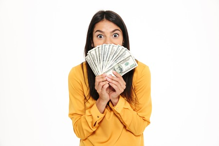 Portrait of an excited woman holding bunch of money banknotes at her face and looking at camera isolated over white background