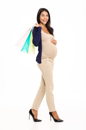 Full length portrait of a young casual pregnant woman walking and carrying shopping bags isolated over white background
