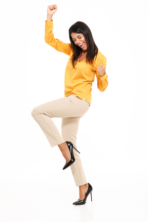 Image of amazing excited young lady in yellow shirt standing isolated over white background make winner gesture.