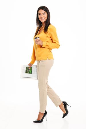 Ganzaufnahme einer glücklichen hübschen Frau, die Tasse Kaffee und eine Zeitung beim Gehen lokalisiert über weißem Hintergrund hält