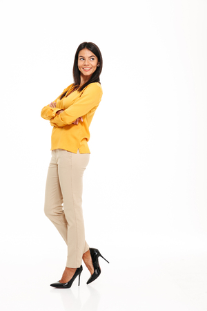 Full length portrait of an attractive confident woman standing with arms folded and looking away at copy space isolated over white background