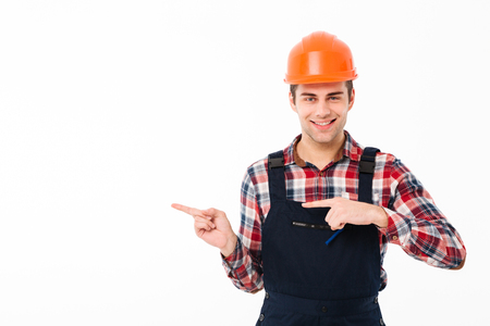Portrait of a smiling young male builder pointing two fingers away while standing and looking at camera isolated over white background