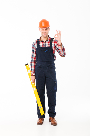 Full length portrait of a cheerful young male builder holding spirit level tool while standing and showing ok gesture isolated over white background Reklamní fotografie