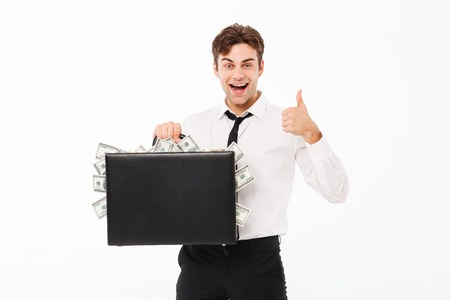 Portrait of a smiling cheery businessman holding briefcase full of money banknotes and showing thumbs up gesture isolated over white background