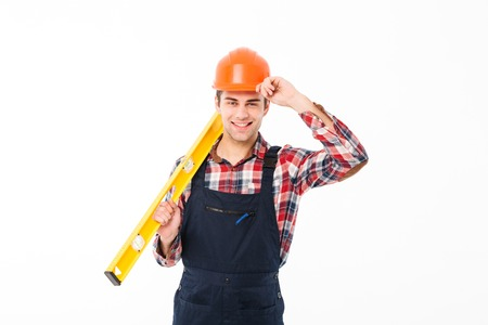 Full length portrait of a happy young male builder holding spirit level tool while standing and looking at camera isolated over white background