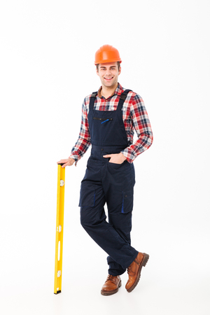 Full length portrait of a smiling young male builder holding spirit level tool while standing and looking at camera isolated over white background