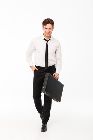 Full length portrait of a confident handsome businessman carrying briefcase while walking and looking at camera isolated over white background