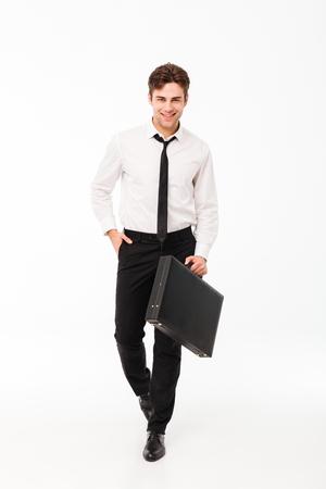 Ganzaufnahme eines überzeugten hübschen Geschäftsmannes , der beim Gehen und Kamera lokalisiert über weißem Hintergrund trägt Standard-Bild - 90373322
