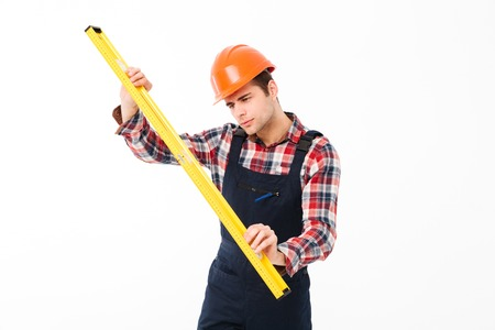 Full length portrait of a concentrated young male builder using spirit level tool while standing isolated over white background Stock Photo - 90373300
