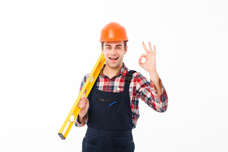 Full length portrait of a successful young male builder holding spirit level tool while standing and showing ok gesture isolated over white background