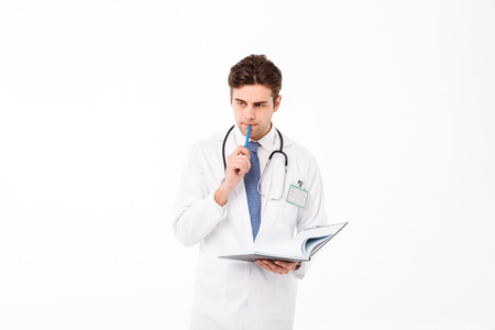 Portrait of a pensive young male doctor with stethoscope dressed in uniform holding a pen with a notebook and looking away isolated over white background