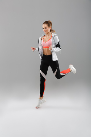 Full length portrait of a concentrated young sportsgirl listening to music with earphones while jogging isolated over gray background