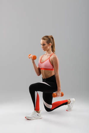 Full length portrait of a confident fit sportsgirl doing exercises with dumbbells while squatting isolated over gray background