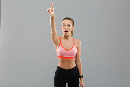 灰色の背景の上に隔離された開いた口で立っている間、コピースペースで指を指差すショックを受けた若いスポーツ少女の肖像画 写真素材
