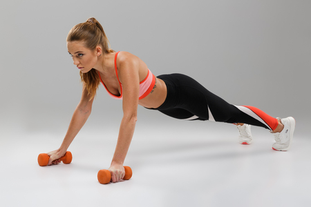 Full length portrait of a confident sportsgirl doing push-ups with dumbbells isolated over gray background Stock Photo