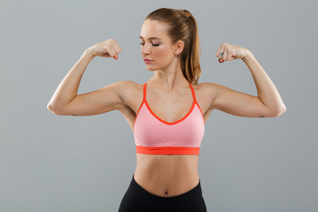 Photo of strong amazing young sports woman standing isolated over grey background. Looking aside showing biceps.