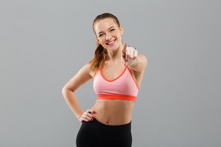Image de la jeune femme heureuse de sport debout isolé sur fond gris . caméra montrant et pointant vers le contact Banque d'images - 90379164