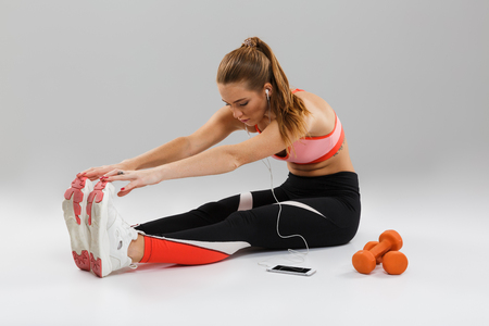 Portrait of a concentrated young sportsgirl listening to music with earphones while sitting on the floor and stretching her leg muscles isolated over gray background