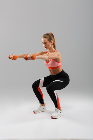 Full length portrait of a focused fit sportsgirl doing exercises with dumbbells while squatting isolated over gray background