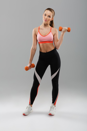 Full length portrait of a young fit sportsgirl doing exercises with dumbbells while standing and looking at camera isolated over gray background