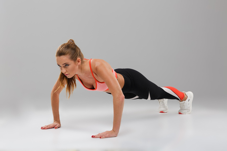 Full length portrait of a young serious sportsgirl doing push-ups isolated over gray background