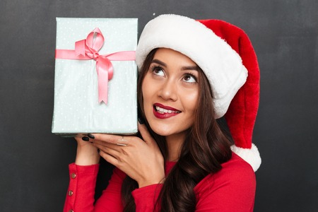 Intrigued smiling brunette woman in red blouse and christmas hat holding gift box and looking up over black background
