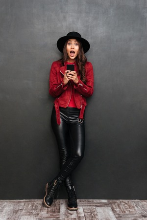 Photo of surprised young woman wearing hat standing over dark grey wall chalkboard chatting by mobile phone. Looking camera. Stock Photo