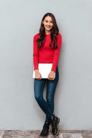 Full length portrait of young beautiful woman in casual wear holding laptop, looking at camera, isolated on gray background Stock Photo