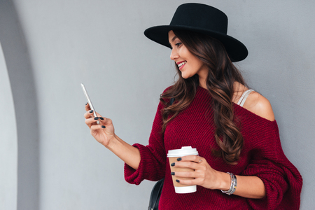 Portrait of a smiling young asian girl dressed in hat and sweater holding coffee cup while standing and using mobile phone on a city street