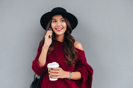 Portrait of a smiling cheerful asian girl dressed in hat and sweater holding coffee cup while talking on mobile phone on a city street