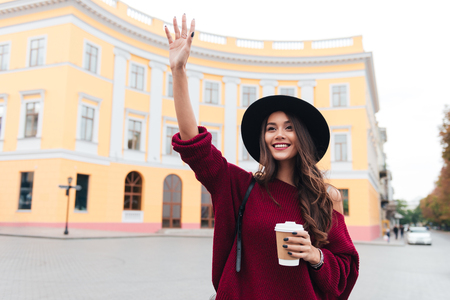Happy brunette woman in hat and sweater waving away and glad to meet outdoors