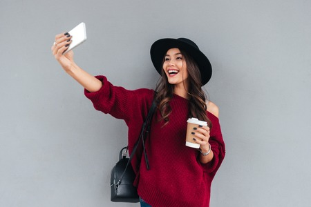 Portrait of a smiling young asian girl dressed in hat and sweater holding coffee cup while taking a selfie outdoors Фото со стока