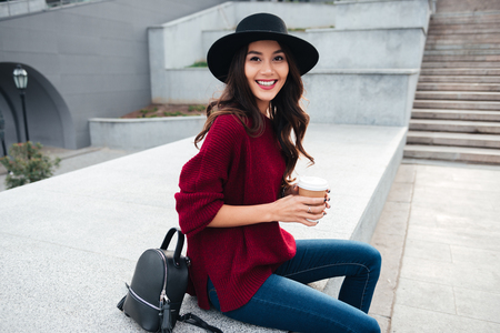 Portrait of a beautiful smiling asian girl wearing hat and sweater holding coffee cup while sitting on a city street