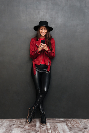 Image of smiling young beautiful woman wearing hat standing over dark grey wall chalkboard chatting by mobile phone. Looking aside.