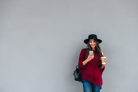 Portrait of a happy asian girl dressed in hat and sweater holding coffee cup while standing and using mobile phone on a city street