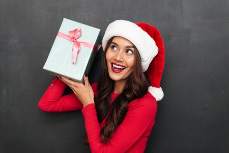 Cheerful intrigued brunette woman in red blouse and christmas hat holding gift box and looking away over black background