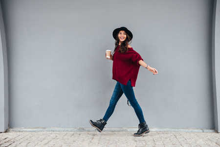 Full length portrait of a smiling joyful asian girl dressed in hat and sweater holding coffee cup while walking on a city street Stockfoto